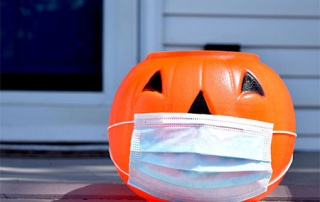 Plastic Halloween pumpkin wearing a mask to represent safe trick-or-treating