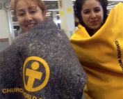 Two young women wrapped in blankets provided by the Church World Service organization